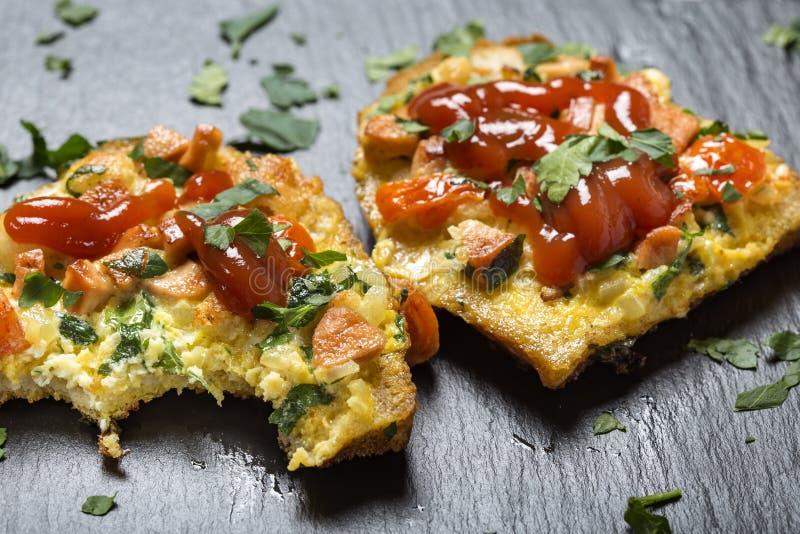 Läckert hemlagat stekt ägg i rostat bröd för frukost med frankfu royaltyfri bild