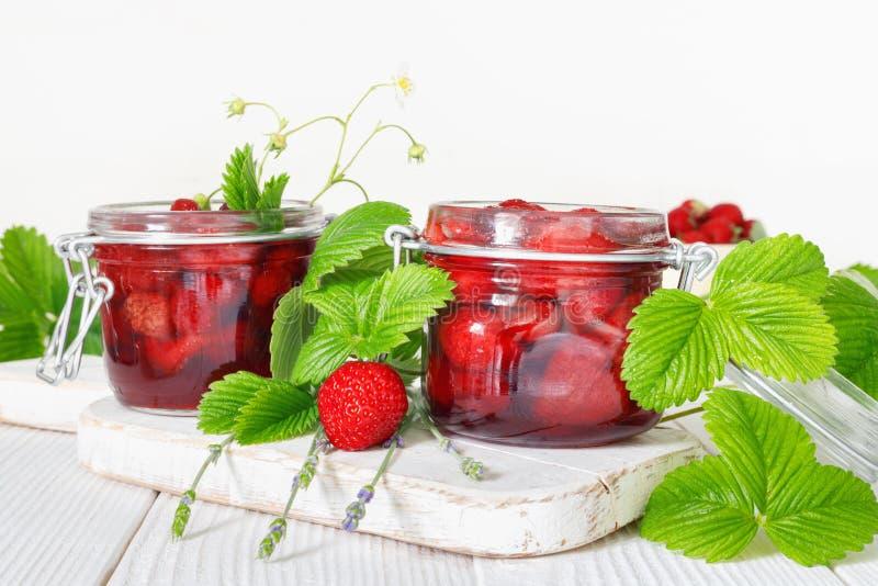 L?ckert jordgubbedriftstopp i traditionell exponeringsglaskrus p? vit tr?bakgrund royaltyfri foto
