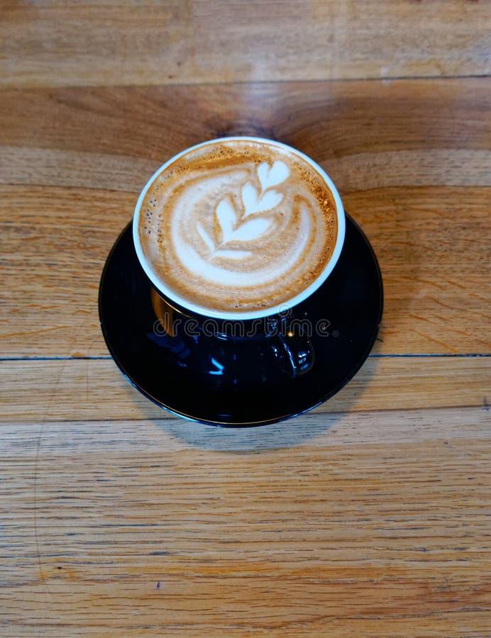 Läckert konstcappuccinokaffe i svart kopp arkivfoto