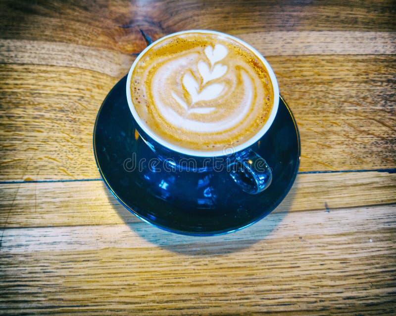 Läckert konstcappuccinokaffe i svart kopp på träbakgrund royaltyfria bilder