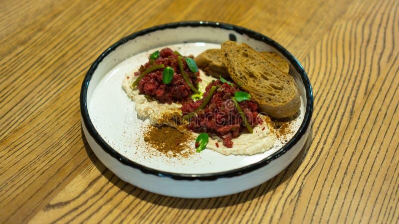 Läckert nötkött som är tartare på en kudde av krämig sås, rostat bröd, kryddor, sparris och högg av lökar på en vit stilfull plat royaltyfria bilder