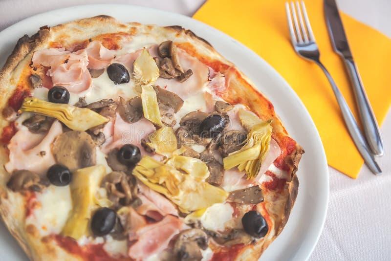 Läckert nytt pizzamål tjänade som på plattan med kniven och gaffel på gul servett Selektivt fokusera arkivbild