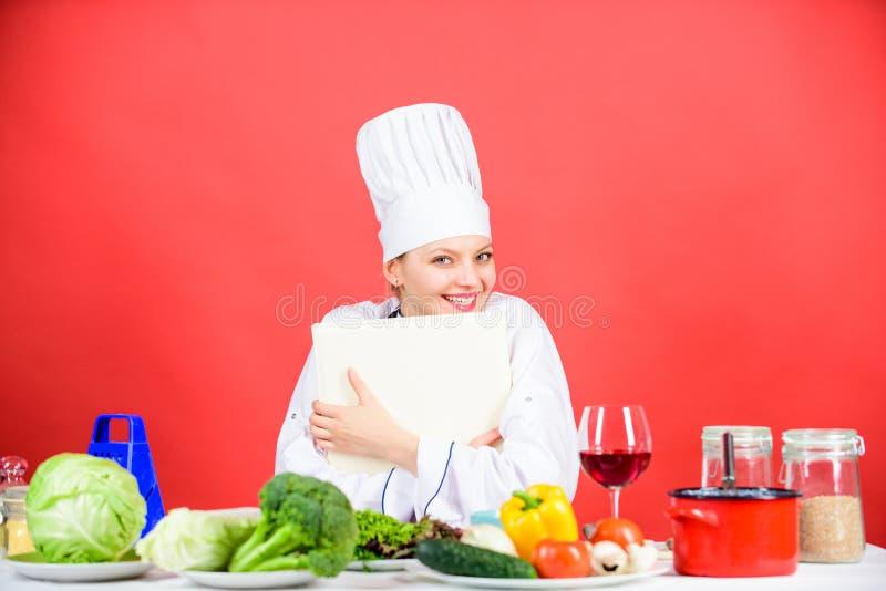 Läckert och gourmet- Laga mat mat som hobby Laga mat att söka efter laga mat recept i kokbok Bok för kvinnaläsningkock in royaltyfri foto