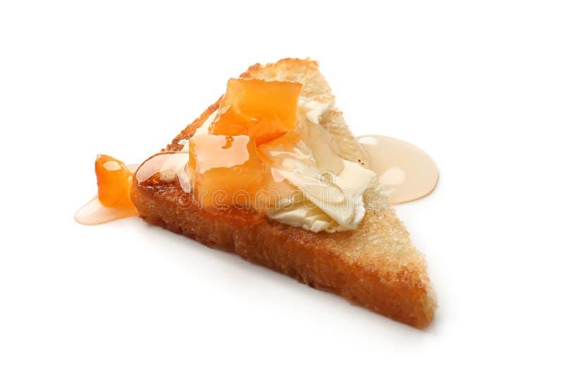 Läckert rostat bröd med smör och på burk frukt på vit bakgrund royaltyfria foton