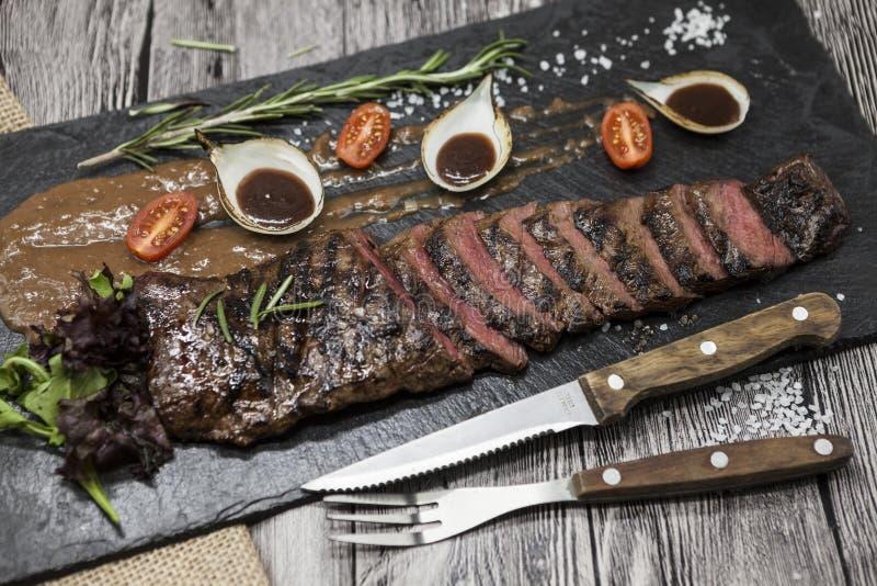 Läckert saftigt varmt steknötkött klippte in i läckra stycken av kött och grönsaker Tjänat som på en svart stenplatta med en gaff arkivbilder