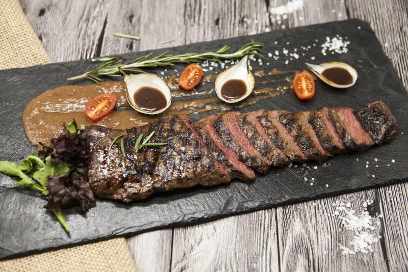 Läckert saftigt varmt steknötkött klippte in i läckra stycken av kött och grönsaker Tjänat som på en svart stenplatta med en gaff royaltyfri foto