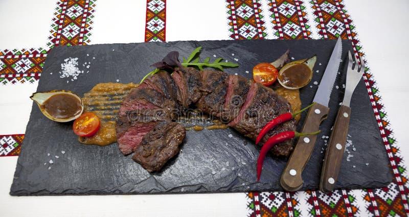 Läckert saftigt varmt steknötkött klippte in i läckra stycken av kött och grönsaker Tjänat som på en svart stenplatta med en gaff fotografering för bildbyråer
