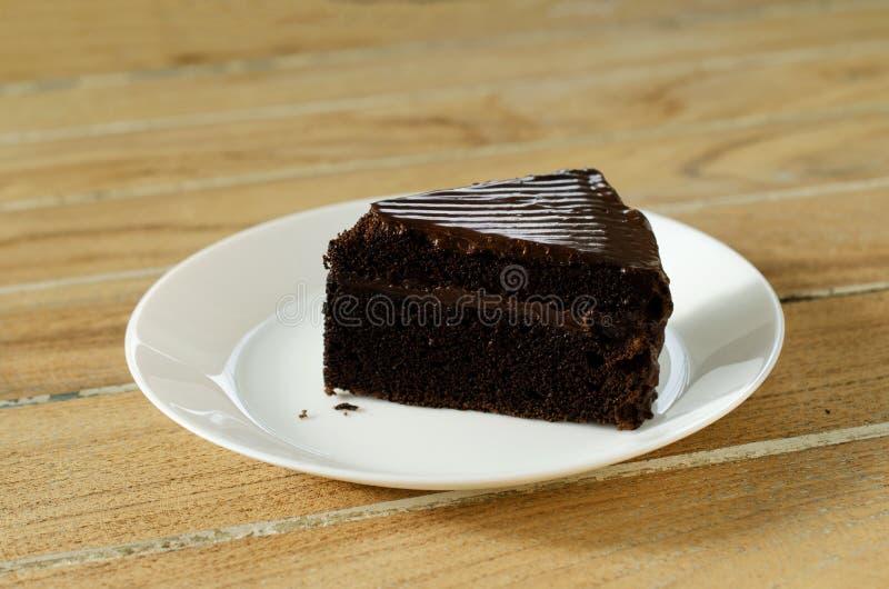 Läckert slut för makro för chokladkaka upp på den vita maträtten och trätabellbakgrunder royaltyfria foton
