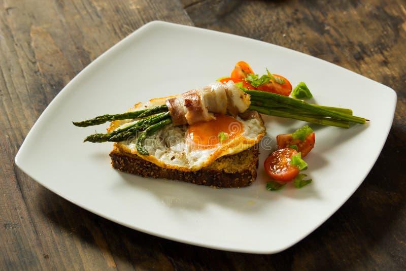 Läckert stekt ägg på ett rostat bröd som täckas med grillad sparris som slås in i bacon på en vit platta fotografering för bildbyråer