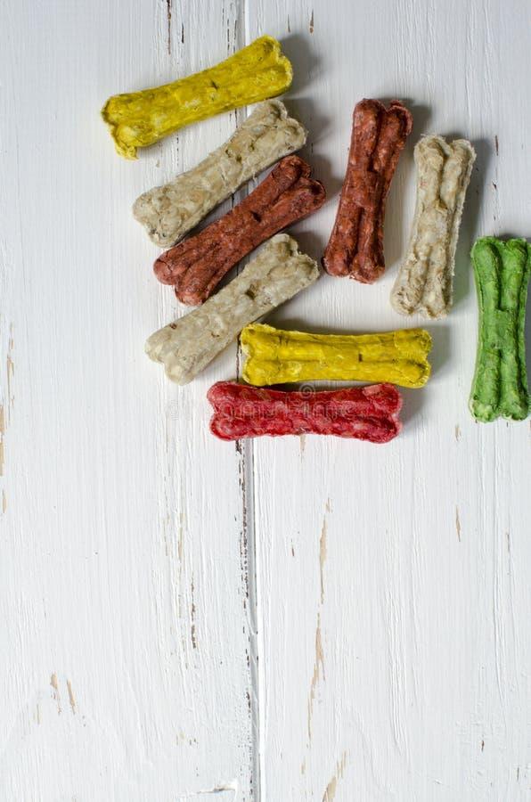 Läckert tugga färgade ben för hundkapplöpning med olika smaker på vit träbakgrund arkivfoton