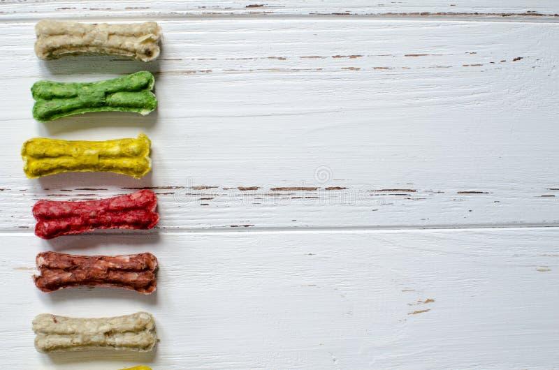Läckert tugga färgade ben för hundkapplöpning med olika smaker på vit träbakgrund royaltyfria bilder