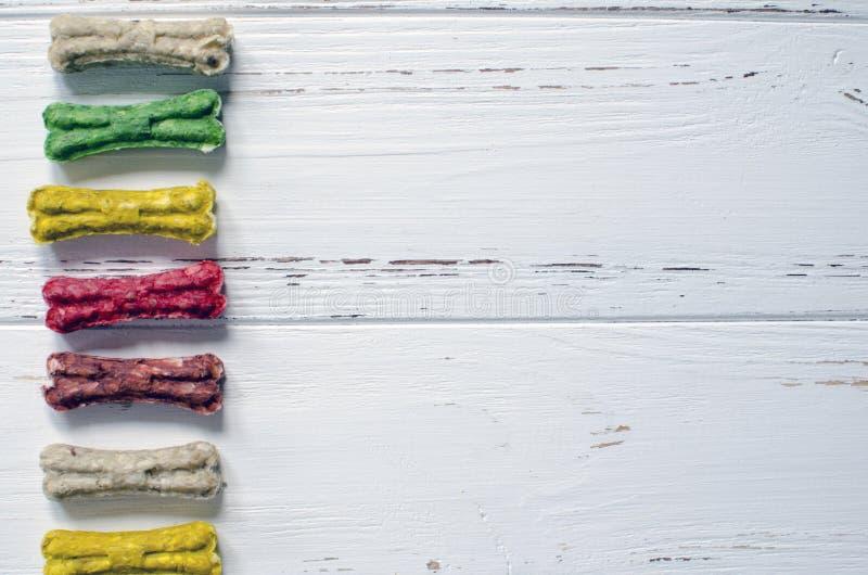 Läckert tugga färgade ben för hundkapplöpning med olika smaker på vit träbakgrund arkivfoto