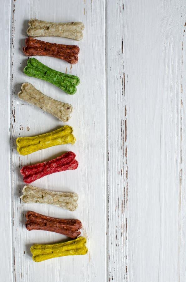 Läckert tugga färgade ben för hundkapplöpning med olika smaker på vit träbakgrund fotografering för bildbyråer