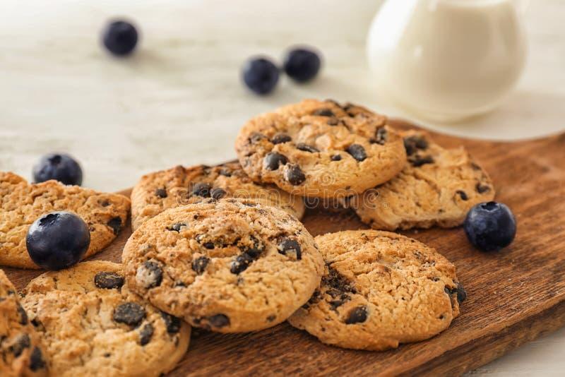 Läckra choklade kakor med nya blåbär på träbräde arkivbild