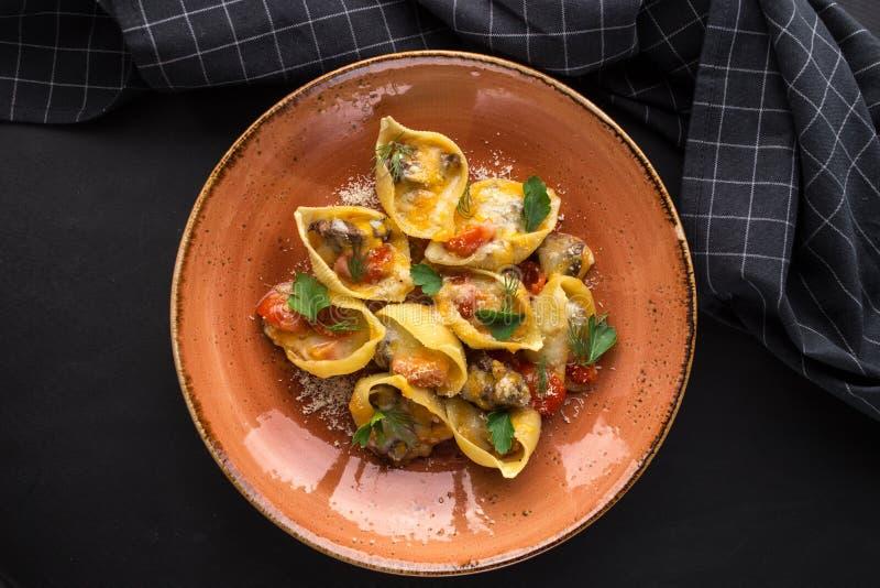 Läckra Conchiglie Giganti pastaskal med kött, körsbärsröda tomater och ost på svart bakgrund royaltyfria foton