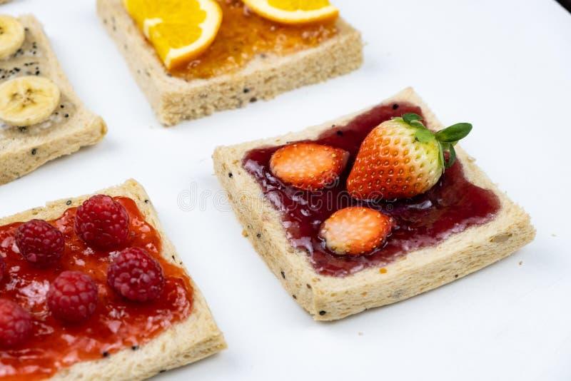 Läckra färgglade minsta blandningfrukter sitter fast på skivat bröd Ställ in på vit bakgrund royaltyfria foton