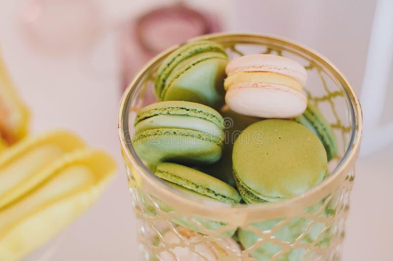 Läckra gröna pistaschmakron, efterrätter och sötsaker på tabellpartiet på bröllopmottagandet Stilfull godisstång Jul och nytt royaltyfri fotografi