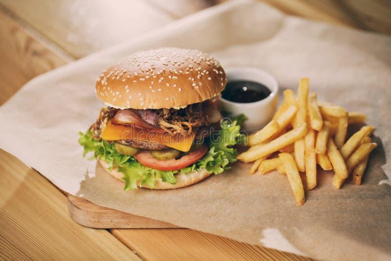 Läckra hamburgare med den nötköttbacon, tomaten, ost och grönsallat arkivbild