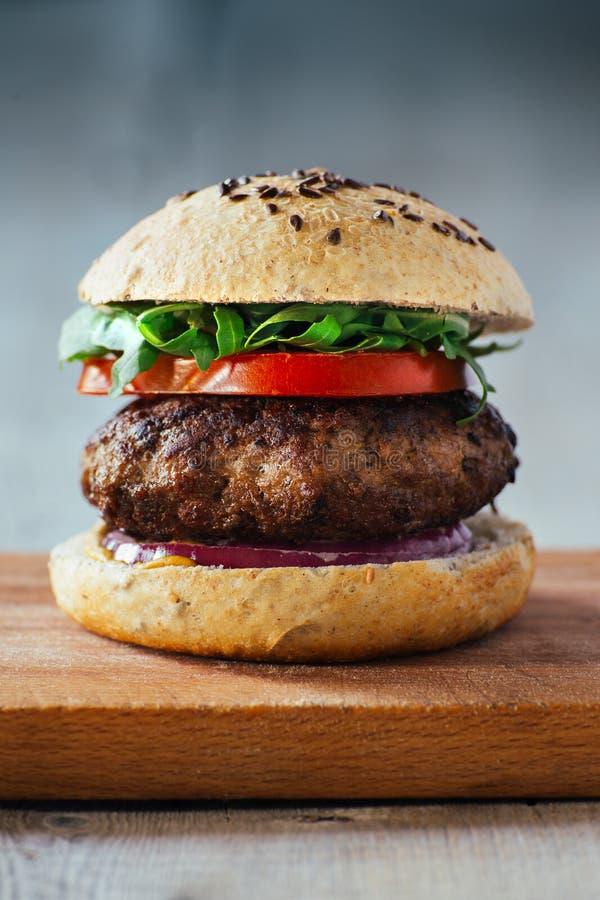 Läckra hamburgare med nötkött, tomaten, ost och grönsallat royaltyfri fotografi