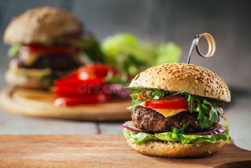 Läckra hamburgare med nötkött, tomaten, ost och grönsallat arkivbild