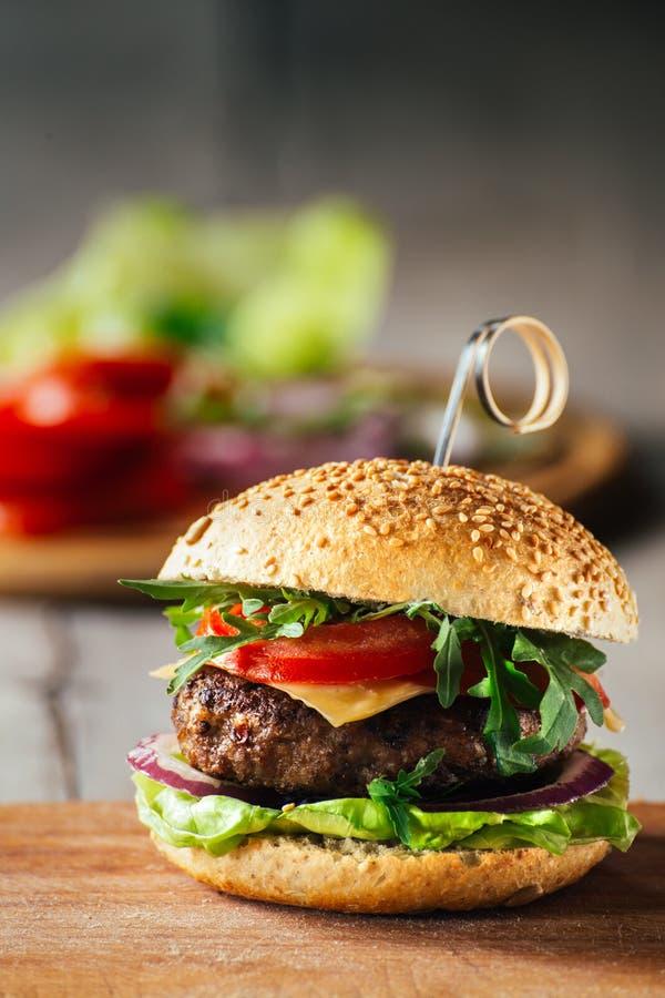 Läckra hamburgare med nötkött, tomaten, ost och grönsallat royaltyfri bild