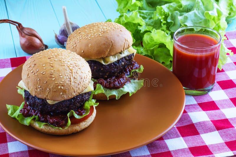 Läckra hamburgare med nötkött, tomaten, ost och grönsallat fotografering för bildbyråer