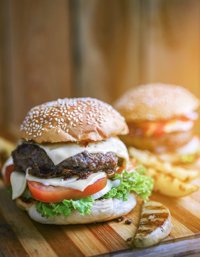 Läckra hamburgare med nötkött, tomaten, ost och grönsallat arkivfoton