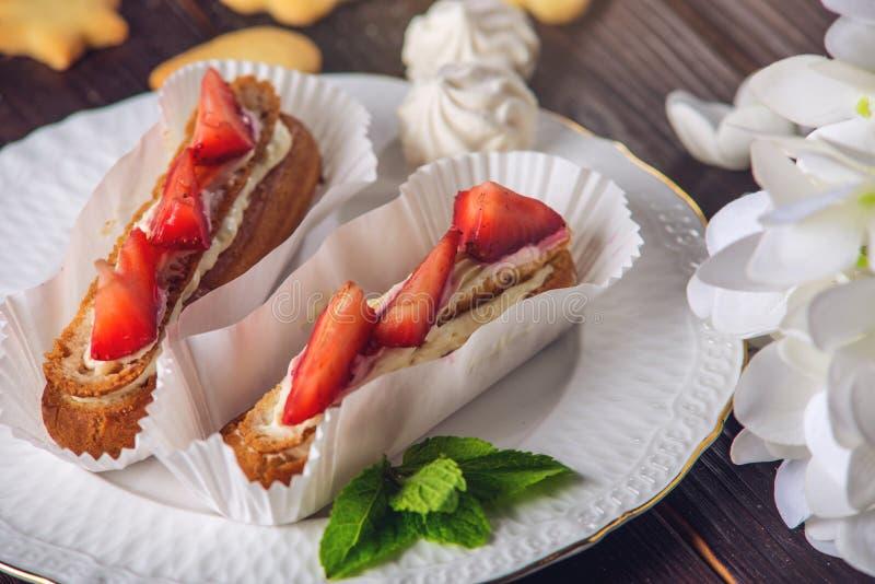 Läckra hemlagade kakaeclairs med jordgubbar och kräm på en träfarstubro och ett stycke på plattan arkivfoton
