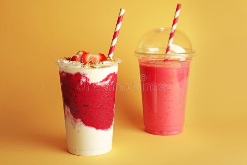 Läckra jordgubbecoctailar i plast- koppar royaltyfria foton