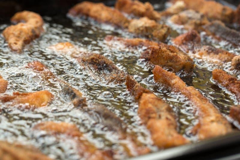 Läckra karpfiléer som grillas i stekpannan arkivbild