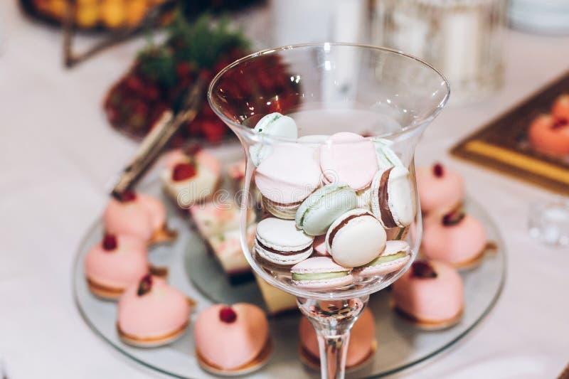 Läckra makron i exponeringsglas och muffin, pop och godis på tabl fotografering för bildbyråer