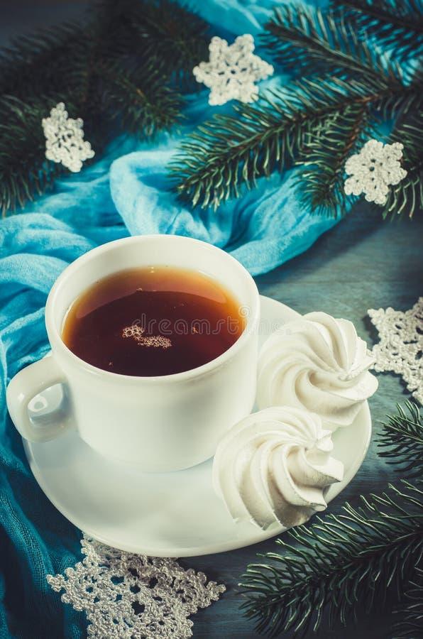 Läckra marängkakor och kopp av varmt te arkivbilder