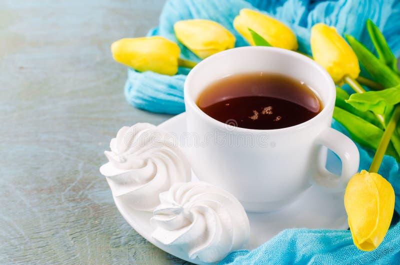 Läckra marängkakor och kopp av varmt te arkivfoton