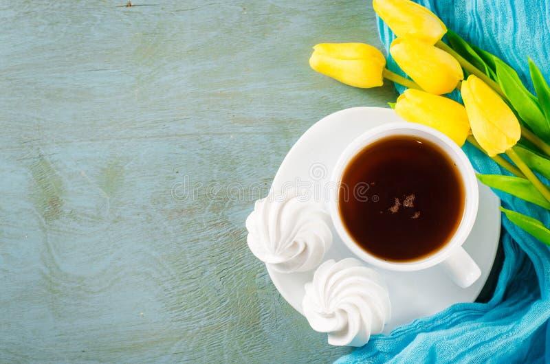 Läckra marängkakor och kopp av varmt te arkivfoto