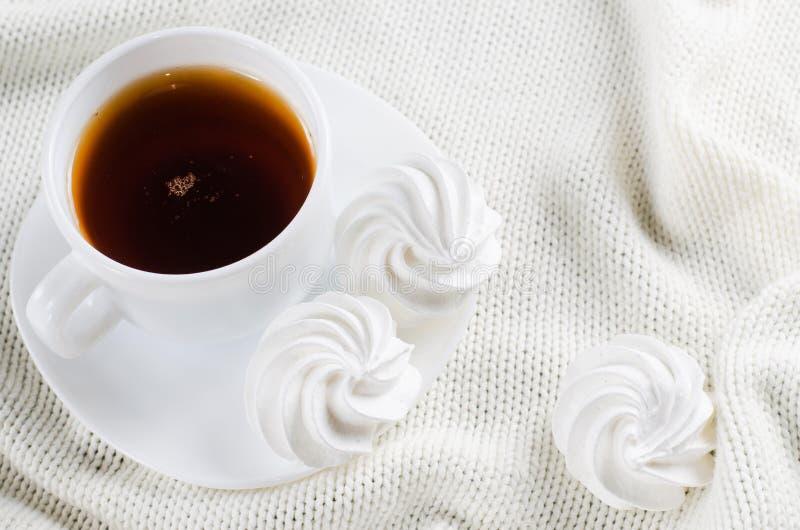 Läckra marängkakor och kopp av varmt te royaltyfri foto
