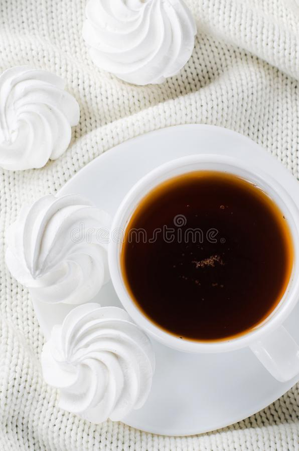Läckra marängkakor och kopp av varmt te fotografering för bildbyråer