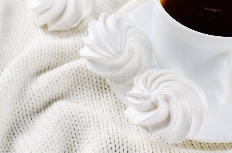 Läckra marängkakor och kopp av varmt te royaltyfria foton