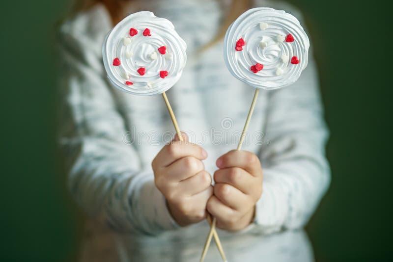 Läckra marängsötsaker med hjärtor i barns händer Begreppet av sötsaker, parti, bageri royaltyfri foto