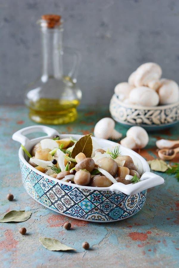 Läckra marinerade champinjoner i en härlig bunke med lökar, peppar, dill och olivolja på enblått bakgrund, bästa sikt arkivfoton