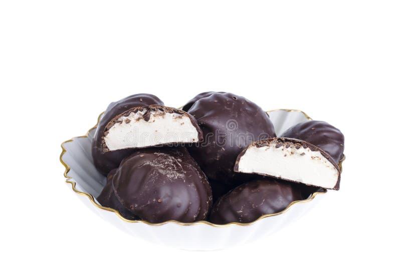 Läckra marshmallower i choklad på plattan white f?r bakgrundschickpeabild royaltyfri fotografi