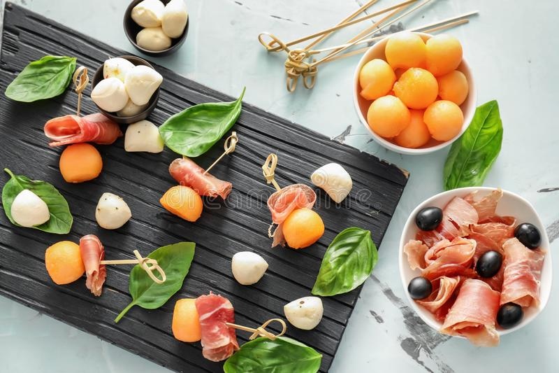 Läckra melonbollar med prosciutto- och mozzarellaost på träbräde arkivbilder