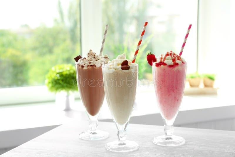Läckra milkshakar på tabellen arkivfoto