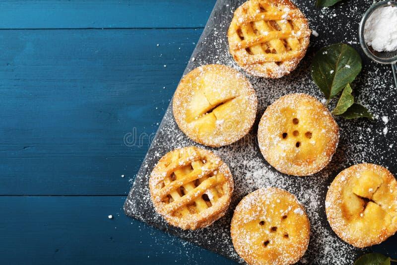 Läckra mini- äppelpajer på blå bakgrund från över Höstbakelseefterrätter arkivfoto