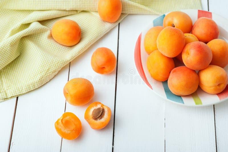 Läckra mogna organiska orange aprikors i en härlig platta dekorerade med den gröna servetten som lägger på den vita trätabellen royaltyfria bilder