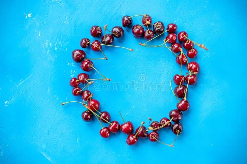 Läckra mogna röda körsbär på den blåa bakgrunden som ordnas i cirkelram Id?rik orientering med nya mogna b?r arkivbilder