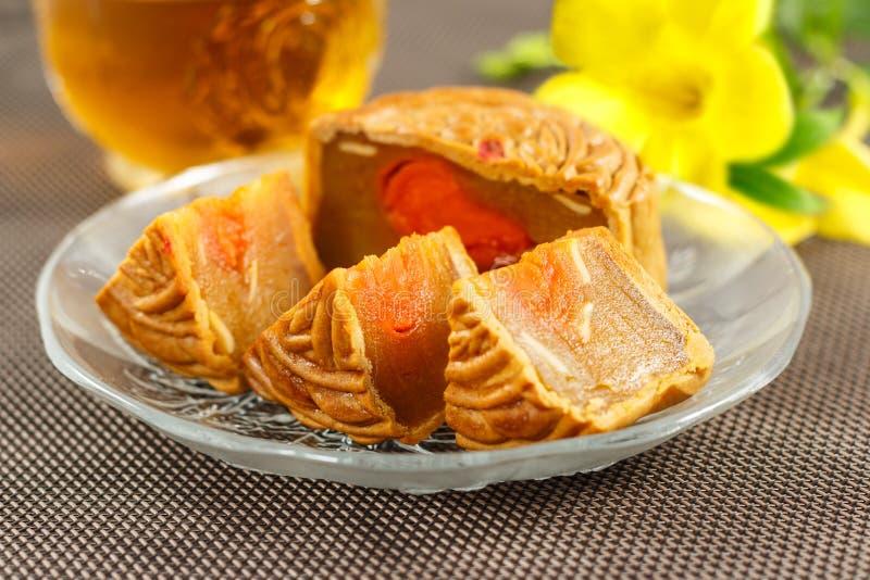 Läckra mooncakes som skivas in i stycken på en glass platta arkivfoto