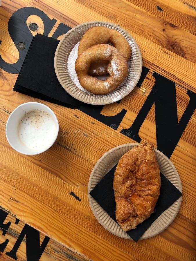 Läckra munkar med pudrat socker och kaffe royaltyfri bild