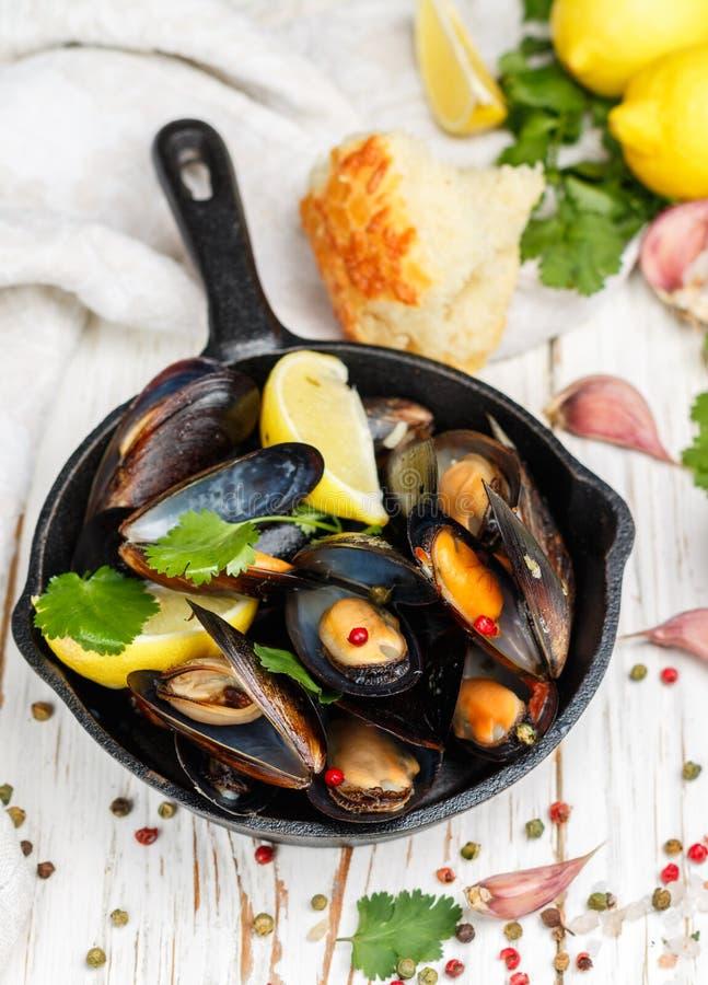 Läckra musslor i vitt vin med citronen, vitlök, örter och kryddor i en gjutjärnkastrull arkivbilder