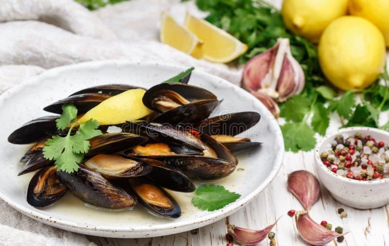 Läckra musslor i vitt vin med citronen, vitlök, örter och kryddor i en vit platta arkivfoton