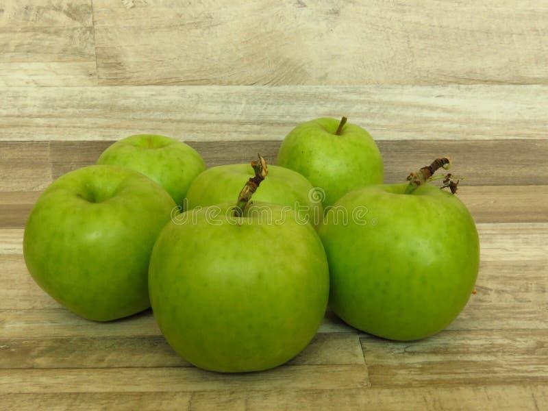 Läckra nya gröna äpplen på bakgrund för tappninggrå färg-vit lantlig stil royaltyfria bilder